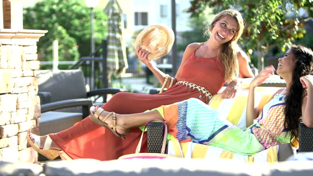 Young multi-ethnic women relaxing, talking on patio video