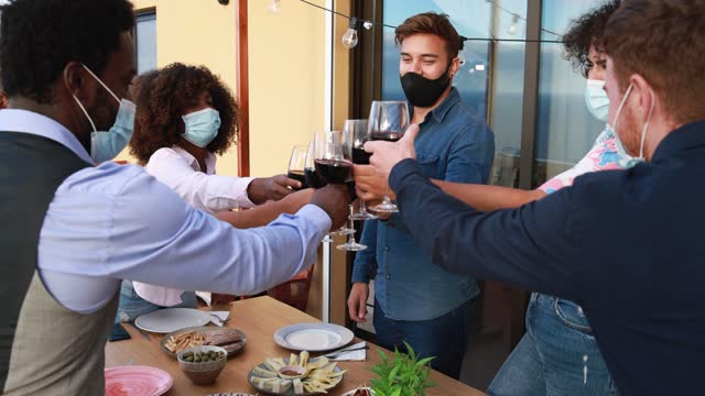 Young multiracial people cheering with wine while wearing protective masks - Social distance concept Young multiracial people cheering with wine while wearing protective masks - Social distance concept holiday event stock videos & royalty-free footage