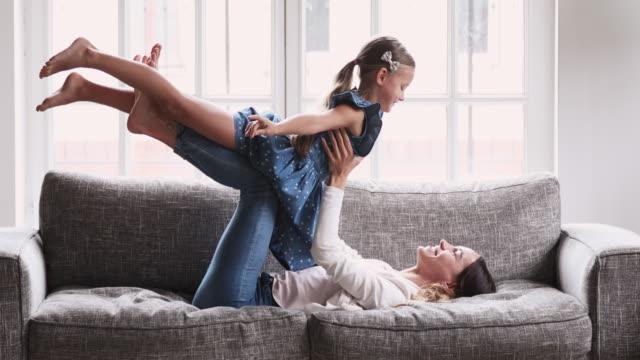 vidéos et rushes de jeune fille d'enfant de levage de maman jouant le jeu d'avion sur le sofa - chrono sport