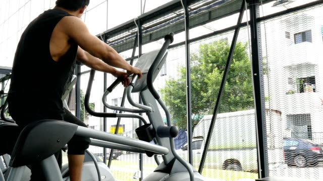 young muscle man execute exercise in fitness center. Asian athlete run on elliptical trainer machine in gym. bodybuilder male working out in health club. sport, training, healthy lifestyle concept video