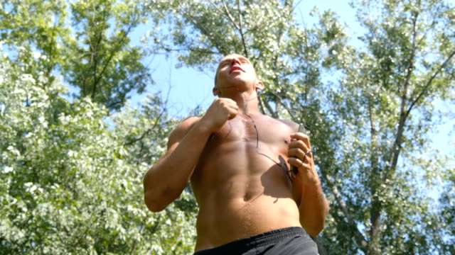 Young muscular athlete running at the forest path. Active strong man training outdoors. Fit handsome athletic male sportsmen working out. Guy training and exercising. Healthy lifestyle. Close up video