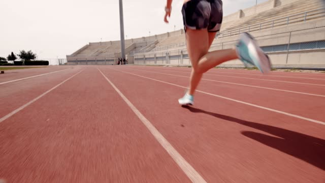 Young muscular athletic woman training and running on sports track
