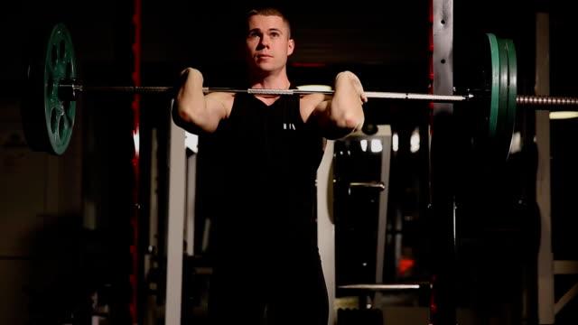vídeos de stock e filmes b-roll de young muscular man at the gym performing squats - agachar se