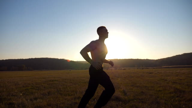 young muscular man running through field with beautiful landscape at background. male athlete trains in nature. soldier jogs at sunset time. unity with nature. healthy active rest. side view slow motion - рядовой стоковые видео и кадры b-roll