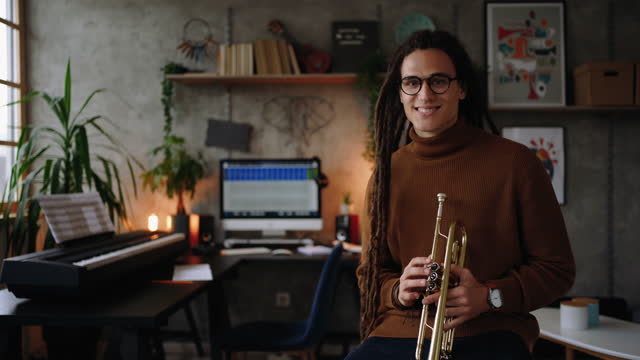 Young musician posing for a photo in his home office studio video