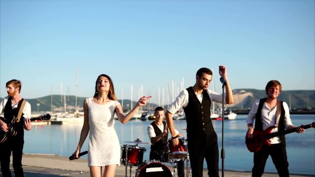 若い音楽家が海のそばの通りに彼らのバンドのコンサートを与える - ミュージシャン点の映像素材/bロール