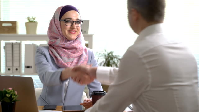 young muslim business woman shake hands with a caucasian man during a meeting in office - abbigliamento religioso video stock e b–roll