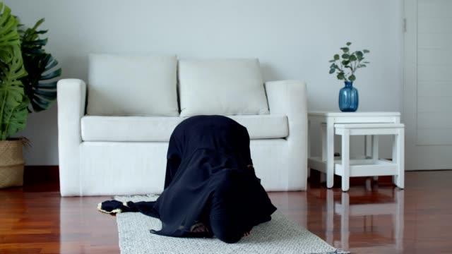 stockvideo's en b-roll-footage met jonge moslim vrouw die het islamitische geloof bidt en oefent - heilig geschrift