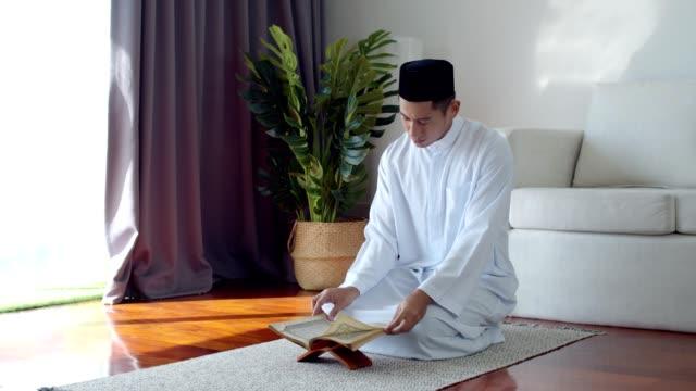 stockvideo's en b-roll-footage met jonge moslim man het dragen van islamitische kleren het lezen van de koran - heilig geschrift