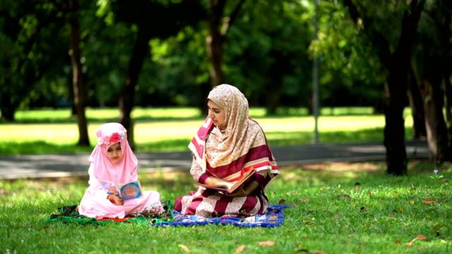 stockvideo's en b-roll-footage met 4k jonge moslim moeder die quran opent en haar dochter leert lezen - koran