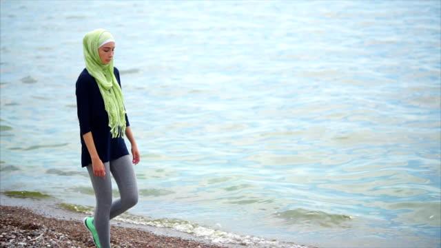 en ung muslimsk kvinna i slöja kommer med en fundersam blick längs havet - anständig klädsel bildbanksvideor och videomaterial från bakom kulisserna
