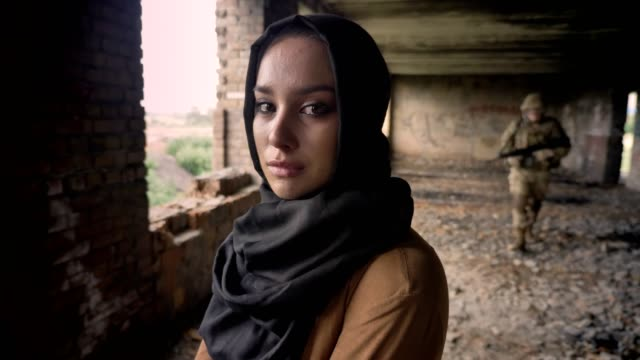 Young muslim woman in hijab crying and looking at camera, soldier with gun walking in background, abandoned building, terrorism concept video