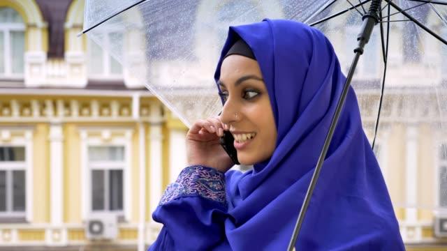 unga muslimska kvinnan i hijab innehar paraply och talar i mobiltelefon, byggnad i bakgrunden - anständig klädsel bildbanksvideor och videomaterial från bakom kulisserna