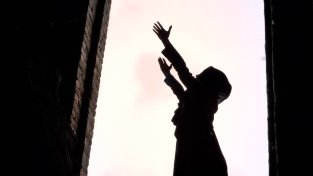 young muslim woman in hijab raising her hands to sky and praying in abandoned building, frightened and terrified - modlić się filmów i materiałów b-roll