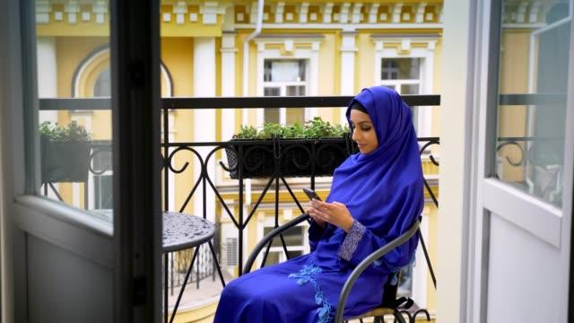 unga muslimska kvinnan i hijab som sitter i stol på balkongen och att skriva på mobilen - anständig klädsel bildbanksvideor och videomaterial från bakom kulisserna
