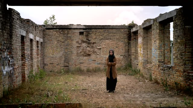 Young muslim woman in hijab standing alone in ruined abandoned brick building Young muslim woman in hijab standing alone in ruined abandoned brick building. eastern europe stock videos & royalty-free footage