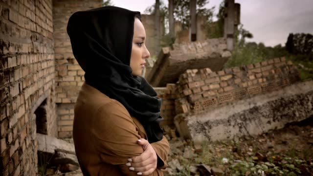 young muslim woman in hijab standing near ruined building and looking at camera with scared and worried expression, ruin in background - libia video stock e b–roll