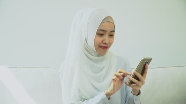 young muslim woman in hijab typing phone - abbigliamento modesto video stock e b–roll