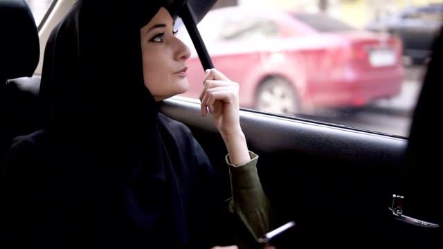 Junge Muslimin schaut ihr Handy während der Fahrt mit dem Auto an. Nachdenklich auf die Straße durch das Autofenster schauen. Frau in schwarzem Hijab – Video