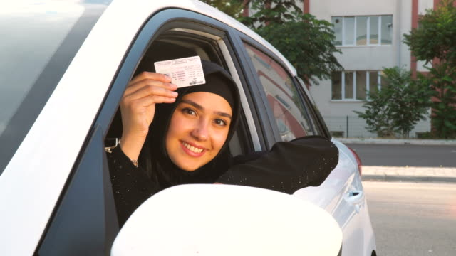 Young Muslim woman showing her driving licence in car