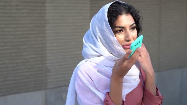 junge muslimische frau trägt hijab sms-nachricht mit ihrem smartphone. - kopfbedeckung stock-videos und b-roll-filmmaterial