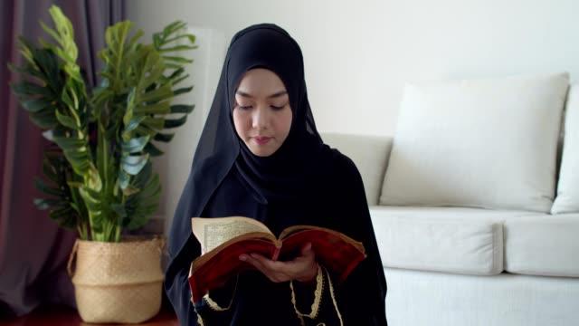 stockvideo's en b-roll-footage met jonge moslim vrouw die traditionele kleding en hijab lezing quran draagt - heilig geschrift