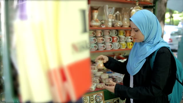 young muslim woman with backpack on summer vacation,watching and buying souvenirs for family - oman filmów i materiałów b-roll