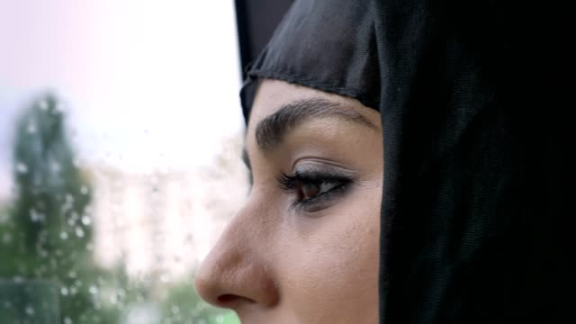Young muslim woman's in hijab eyes is watching in rainy window in bus, weather concept, transport concept, urban concept, dreaming concept, side view Young muslim woman's in hijab eyes is watching in rainy window in bus, weather concept, transport concept, urban concept, dreaming concept, side view. middle east stock videos & royalty-free footage