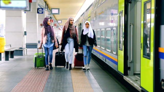 Young muslim women at train station leaving for a journey video