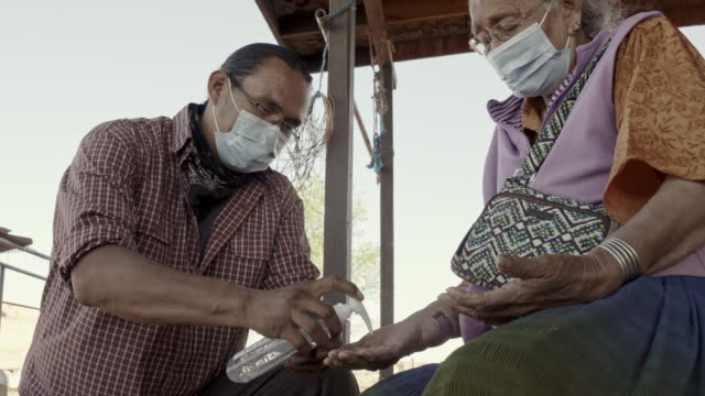 A Young Navajo Man Applying Hand Sanitizer For His Grandmother To Help Protect Her From Coronavirus A Navajo grandmother allowing her grandson to help apply hand sanitizer to protect her from Covid19 indian family stock videos & royalty-free footage