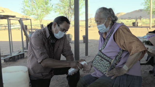 A Young Navajo Man Applying Hand Sanitizer For His Grandmother To Help Protect Her From Coronavirus A Navajo grandmother allowing her grandson to help apply hand sanitizer to protect her from Covid19 minority groups stock videos & royalty-free footage