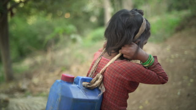 Young Nepali girl carries large jug of water Hand-held camera view poverty stock videos & royalty-free footage