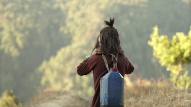 ヘッド ・ ストラップで水差しを運ぶ若いネパール語の女の子 - ネパール点の映像素材/bロール