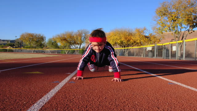 Young Nerd Boy at Track Doing Pushups A young nerd boy dressed in retro track suit and headbands attempts pushups on the running track ready to live a healthy lifestyle. He is eager to stretch and exercise while finding his inner mojo. Image taken in Tempe, Arizona. push ups stock videos & royalty-free footage