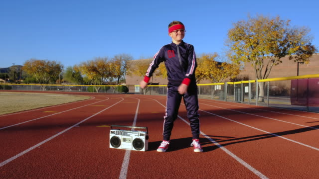 Young Nerd Boy at Track Hip-Hop Dancing A young nerd boy dressed in retro track suit and headband attempts to dance on the running track. He is eager to warm up, stretch, lead a healthy lifestyle and exercise. 4K video taken in Tempe, Arizona. individuality stock videos & royalty-free footage
