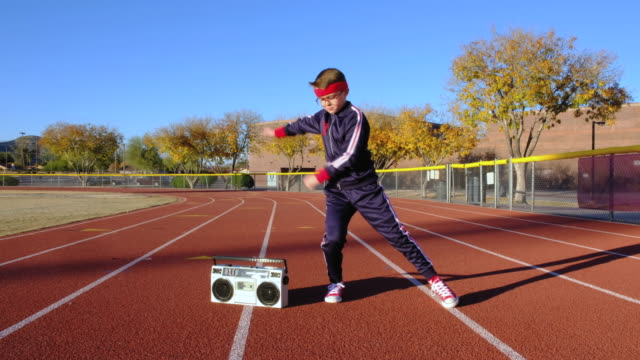 Young Nerd Boy at Track Hip-Hop Dancing A young nerd boy dressed in retro track suit and headband attempts to dance on the running track. He is eager to warm up, stretch, lead a healthy lifestyle and exercise. 4K video taken in Tempe, Arizona. only boys stock videos & royalty-free footage