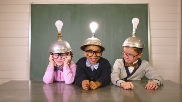 Young Nerds Think while Wearing Idea Helmets Three young children dressed as nerds with homemade thinking caps intensely search for that new big idea. The boy with the light bulb helmet in the middle succeeds with a great idea and his light comes on while the others react with envy. chance stock videos & royalty-free footage