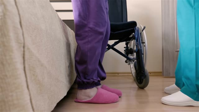 young nurse caring of elder disabled woman in wheelchair - senior care stock videos and b-roll footage