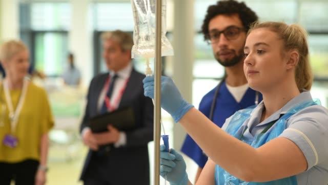 vidéos et rushes de jeune infirmière vérifie iv goutte à goutte - infirmier