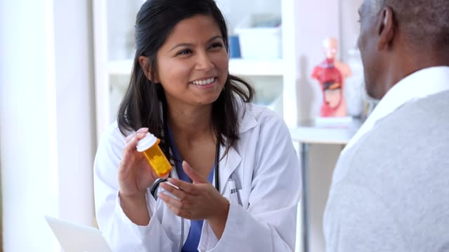 Young nurse in lab coat talks with a mature male Young, female nurse in a lab coat, talks with a mature, senior, adult man about the medicine she is prescribing. She explains how to use it and answers his questions concerning it. She gestures and smiles as she speaks with him. body care stock videos & royalty-free footage