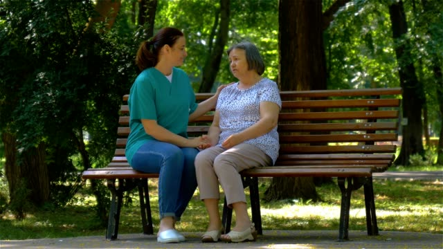 Young nurse spending sunny day with senior woman in park video