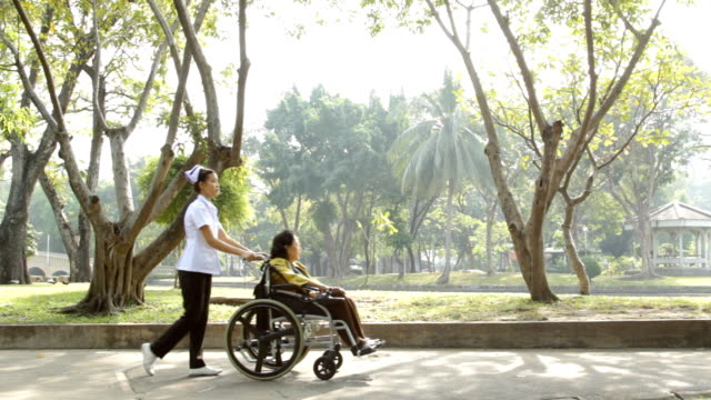 Young nurse take caring old woman on wheelchair video