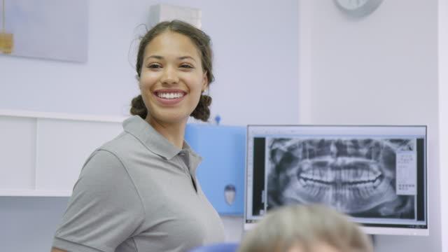 ungsjuksköterska vända och leende på tandläkare - two dentists talking bildbanksvideor och videomaterial från bakom kulisserna
