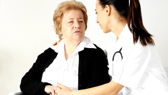 Young  nurse with her senior female patient. video