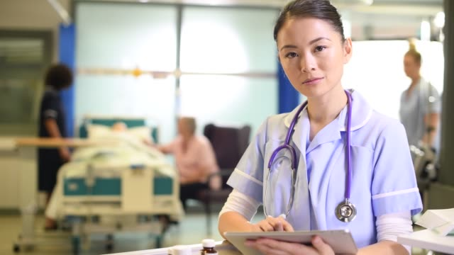 young nurse with meds trolley young nurse adding some digital patient notes nhs stock videos & royalty-free footage
