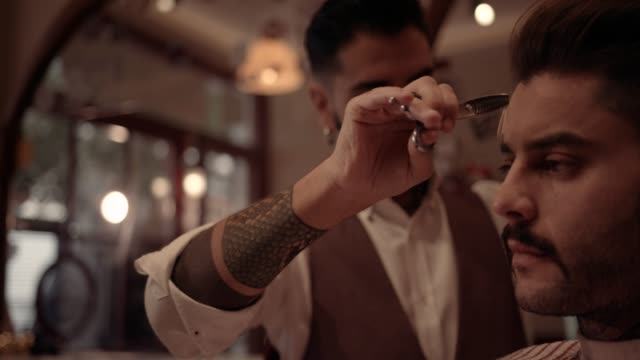 Young old-fashioned stylish barber giving hipster man haircut video