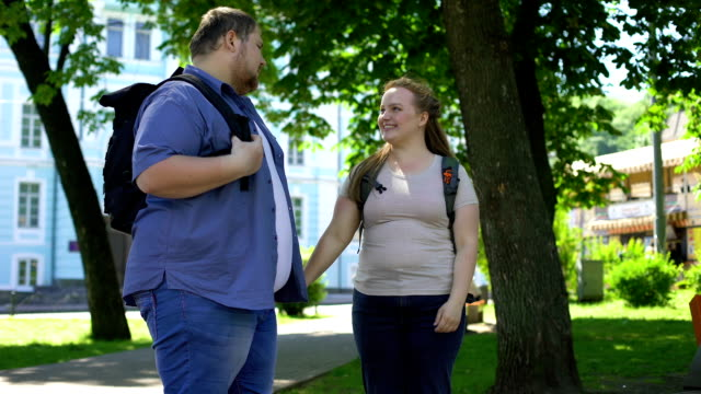 young overweight man and woman holding hands and nuzzling in park, students love - compagni scuola video stock e b–roll