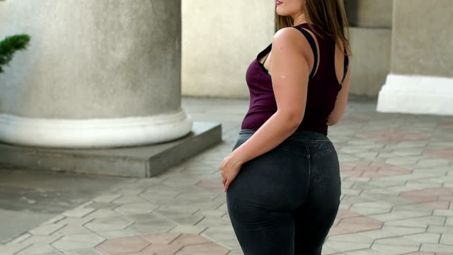 Young overweight woman walking in the city Park, slow motion. Plus size model.