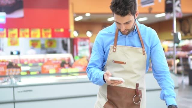 vídeos de stock e filmes b-roll de young owner / employee using mobile phone at supermarket - avental