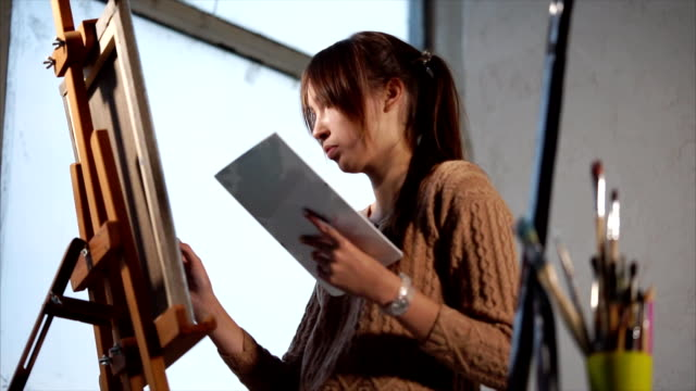 Young painter is deep into the process of drawing. video